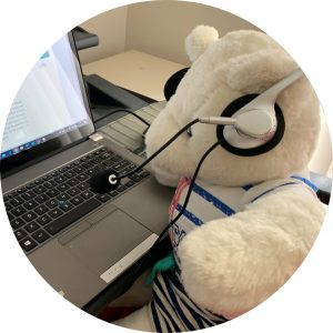 The photo shows SPEVI bear, dressed in casual blue striped shirt and shorts, sitting at a desk with a laptop and wearing headphones. The SPEVI website is up on the screen of his laptop and shows the announcement 'Virtual SPEVI 2021 Conference!'